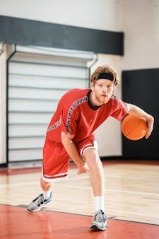 Buen jugador. hombre de jengibre en una ropa deportiva roja jugando baloncesto