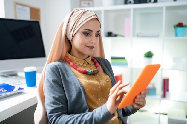Buen maquillaje. hermosa mujer musulmana con maquillaje agradable con su tableta naranja leyendo un libro electrónico