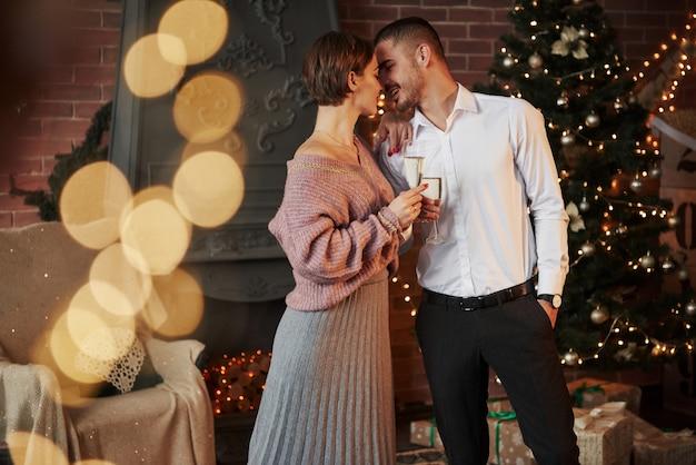 Buen pasatiempo bonita pareja celebrando año nuevo delante del árbol de navidad