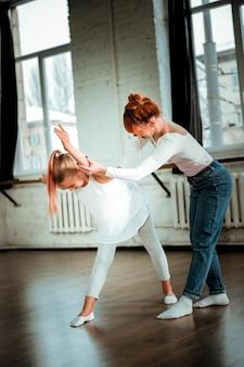 Buen profesor de baile. profesora de danza moderna profesional con cabello rojo que parece involucrado mientras trabaja con el estudiante