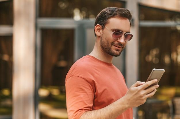 Buen punto. hombre adulto joven satisfecho con gafas de sol y camiseta leyendo el mensaje en el teléfono inteligente de pie al aire libre en la zona de recreación