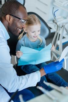 Buen resultado. niña linda sentada en la silla del dentista y mirándose en el espejo después del tratamiento mientras su agradable dentista lo sostiene para ella