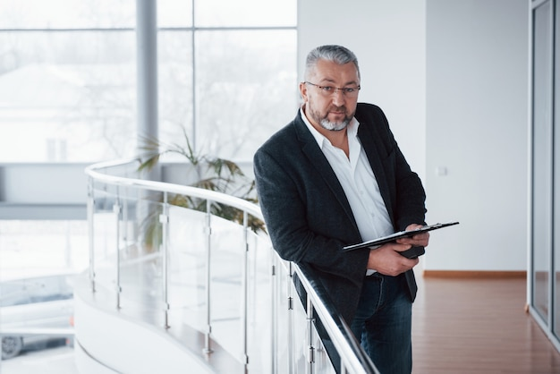 Buen retrato foto del empresario senior en la espaciosa habitación con plantas detrás. sosteniendo y leyendo documentos