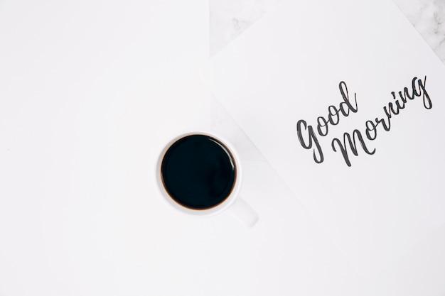 Buen texto de la mañana en el papel con la taza de café contra el fondo blanco