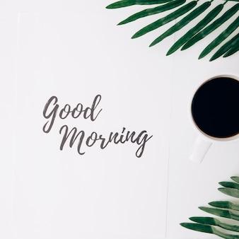 Buen texto de la mañana en el papel con la taza de café y las hojas contra el fondo blanco