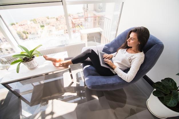 Buen tiempo en casa. hermosa mujer sonriente joven que trabaja en la computadora portátil mientras está sentado en una silla grande y cómoda en casa