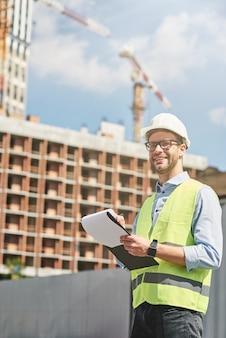 Buen trabajo joven ingeniero civil feliz o supervisor de construcción con casco mirando a otro lado y