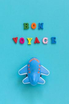 Buen viaje y avión divertido del juguete de los niños en fondo azul. concepto viajes, turismo.