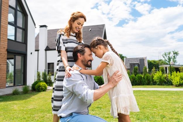Buena chica positiva mirando a su padre mientras está de pie en el césped frente a su casa