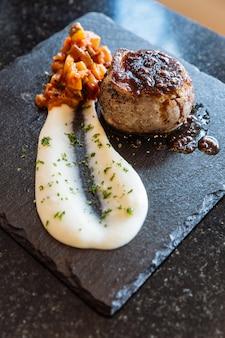 Buena comida: mini filete de ternera con salsa de carne servido con puré de papas y ensalada.