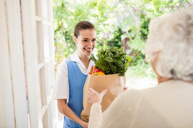 Buena enfermera llevando verduras a un paciente viejo en casa