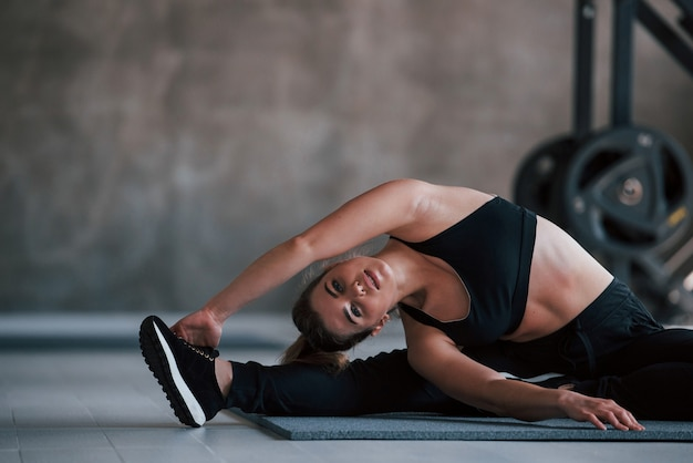 Buena flexibilidad. hermosa mujer rubia en el gimnasio en su tiempo de fin de semana.