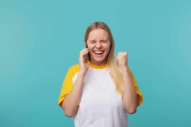 Buena joven feliz dama de cabeza blanca con peinado casual escuchando buenas noticias y regocijándose con los ojos cerrados, de pie en azul