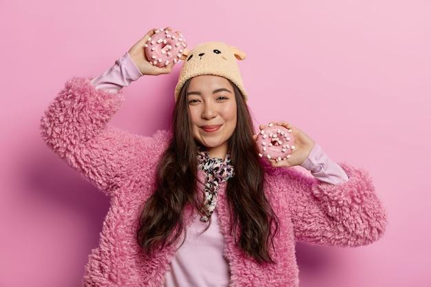 Buena mujer asiática feliz de olvidarse de la dieta, come alimentos azucarados no saludables, sostiene donas en las manos, baila contra el espacio rosado pastel