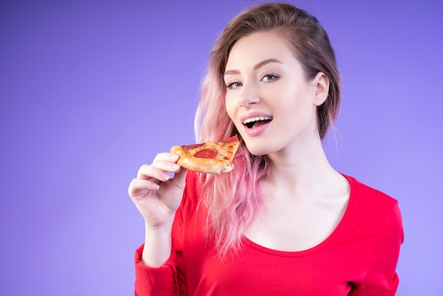 Buena mujer comiendo una rebanada de pizza