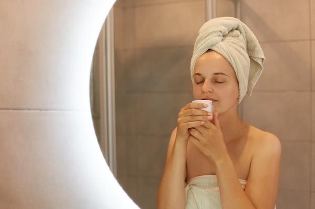 Buena mujer envuelta en una toalla blanca después de tomar una ducha de pie frente al espejo con los ojos cerrados, oler la nueva crema, cuidado de la piel, cosmetología, procedimientos matutinos.
