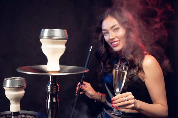 Buena mujer fumando shisha y bebiendo cócteles en un bar
