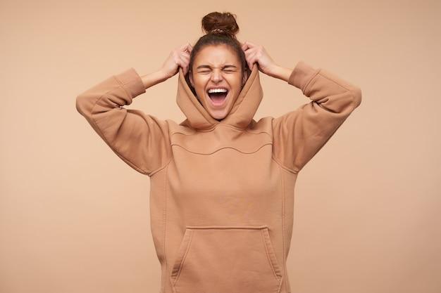 Buena mujer joven y bonita morena que mantiene los ojos cerrados mientras se ríe felizmente, levantando la mano hacia su capucha mientras está de pie contra la pared beige