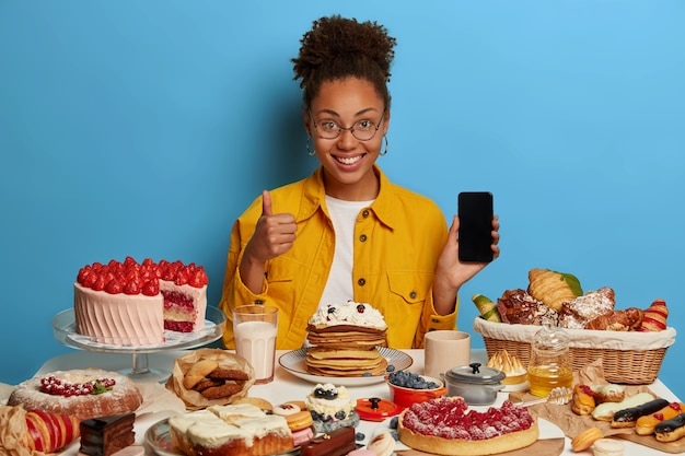 Buena mujer rizada optimista con cabello rizado peinado levanta el pulgar, muestra un dispositivo moderno con pantalla de maqueta, disfruta de una comida sabrosa, come deliciosos dulces recién horneados