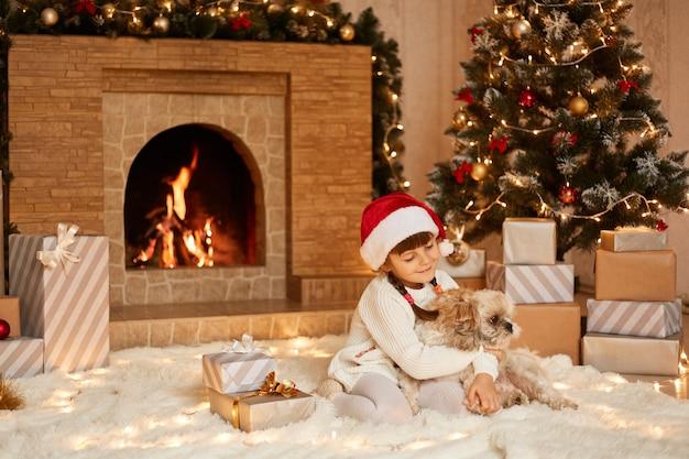 Buena niña jugando con su perro pequinés, niña vestida con suéter blanco y sombrero de santa claus, posando en la sala festiva con chimenea y árbol de navidad.