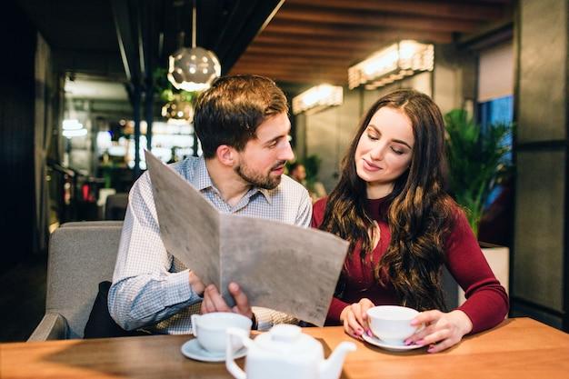 Buena pareja están sentados juntos en un restaurante. ella está tomando un té y mirando un menú mientras su biyfriend está tratando de recoger comida para ellos. también le está dando consejos de comida.
