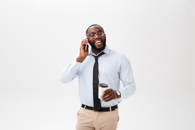 Buena plática. hombre africano joven alegre en la camisa blanca que sostiene una taza de café y que habla en el teléfono móvil