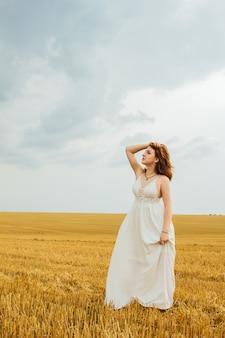 Buena recreación al aire libre. mujer joven hermosa pelirroja en medio de un campo de trigo, divirtiéndose. paisaje de verano, buen clima. día ventoso con el sol y las nubes. vestido de algodón blanco, estilo ecológico.