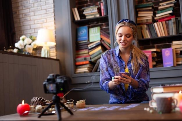 Buena señal. mujer alegre positiva leyendo cartas del tarot mientras graba un video