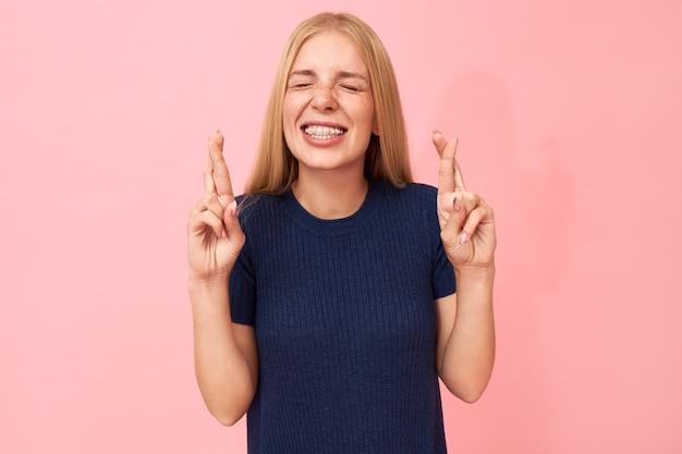 ¡buena suerte! cintura para arriba retrato de divertida adorable adolescente supersticiosa con soportes de dientes haciendo gestos con la mano, cruzando el dedo medio sobre el índice, deseando buena suerte