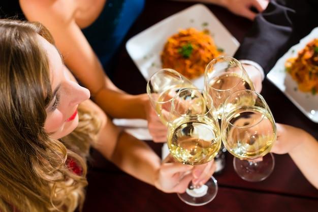 Buenos amigos para cenar o almorzar en un buen restaurante, tintinear vasos