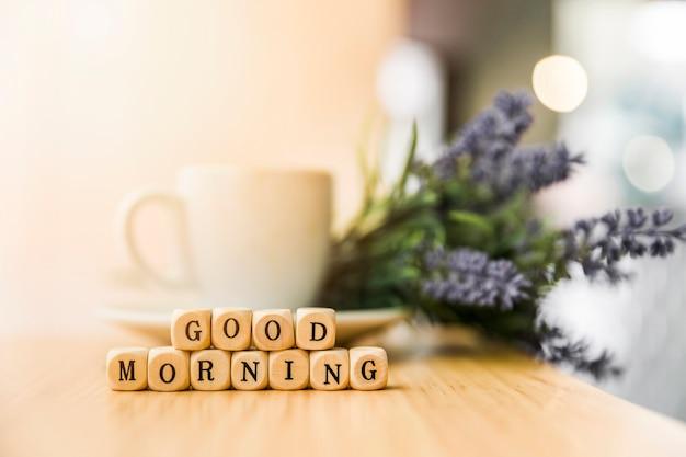 Buenos días bloques cúbicos con taza de café y flores en la mesa de madera