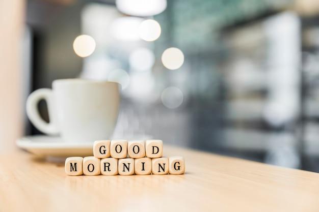 Buenos días bloques cúbicos con taza de café en el escritorio de madera