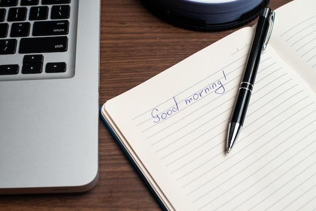 Buenos días con cuaderno y bolígrafo negro con laptop.