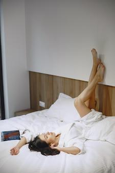 Buenos días. mujer en una cama. señora en el dormitorio. morena con tableta.