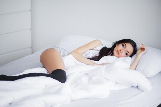 Buenos días, retrato de una sonriente mujer morena bastante joven relajándose en una cama blanca