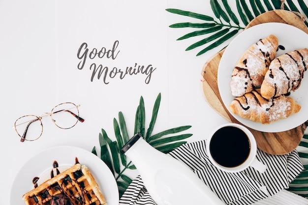 Buenos días texto con anteojos; croissant recién horneado; waffles botella y taza de café en el escritorio blanco