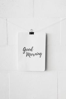 Buenos días, texto en papel, con clip de bulldog sobre la pared blanca.