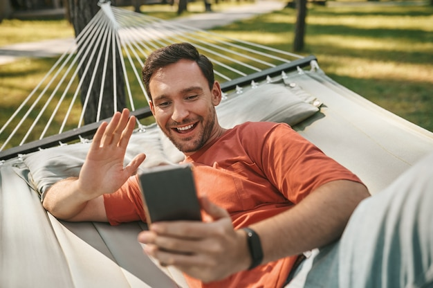 Buenos momentos. feliz joven adulto confiado que se comunica por videollamada en el teléfono inteligente tumbado en una hamaca en el área de recreación al aire libre