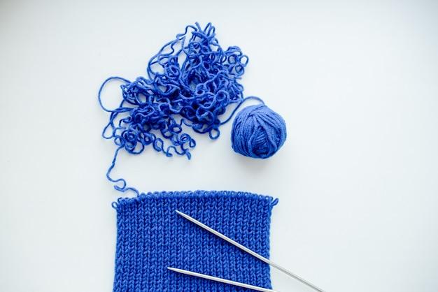 Bufanda azul brillante con agujas de tejer. en whitebackground. concepto de pasatiempo y tiempo libre. vista horizontal superior