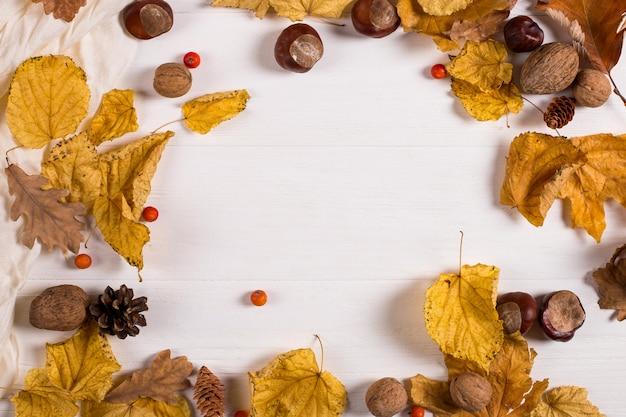 Bufanda, castañas, nueces y hojas secas sobre una mesa de madera. fondo de otoño, copyspace.