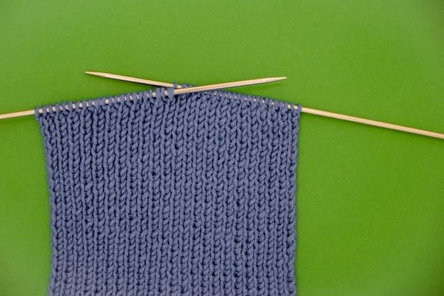 Bufanda hecha punto gris oscuro con agujas de tejer fondo verde.