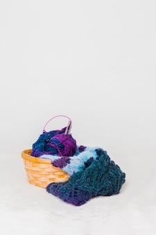 Bufanda de lana y bola con agujas de punto en la cesta de mimbre sobre fondo blanco