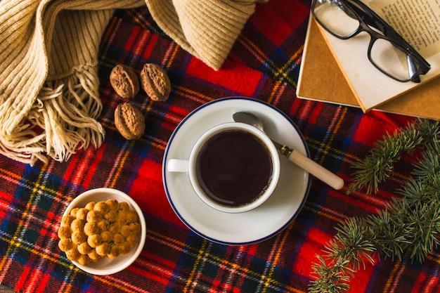 Bufanda y libros cerca de té y aperitivos