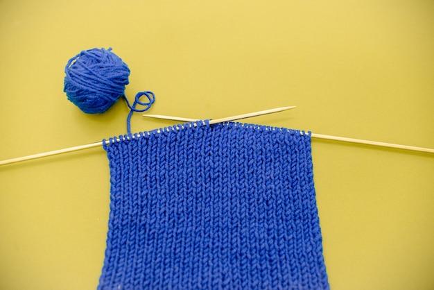 Bufanda de punto azul brillante con agujas de tejer fondo amarillo claro