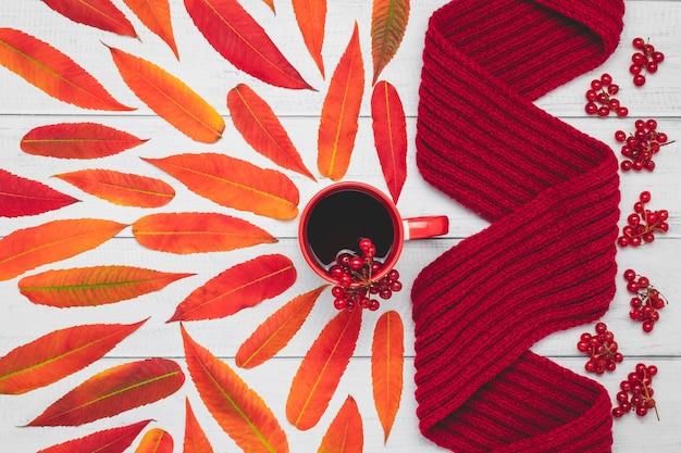 Bufanda de punto caliente y taza de té con hojas rojas sobre tabla de madera, composición de otoño.