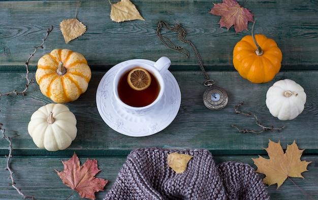 Una bufanda de punto, hojas de otoño, calabazas blancas y naranjas, una taza de té con limón y un viejo reloj de bolsillo.