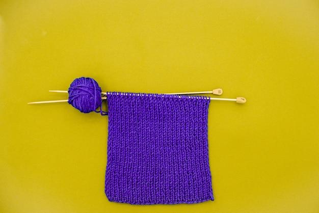 Bufanda de punto morado con agujas de tejer y contraste de color de bola de hilo