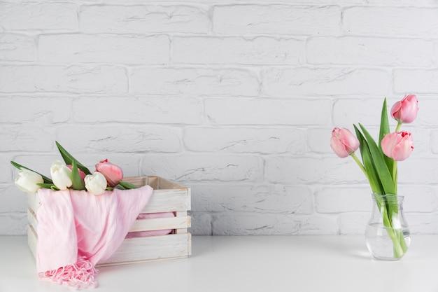 Bufanda rosada dentro de la bufanda de madera y jarrón de tulipanes en el escritorio contra la pared de ladrillo blanco