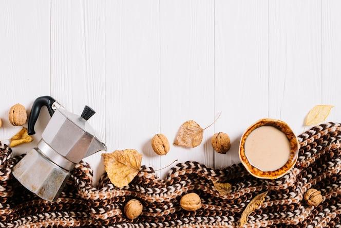 Bufanda y hojas cerca de café y nueces