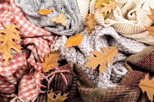 Bufandas calientes y hojas de fondo